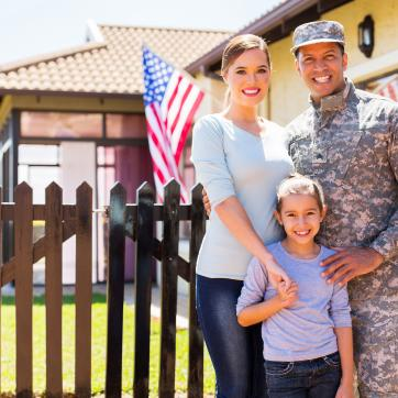 military dad posing with wife and daughter